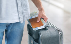 Man Holding His Passport And Carrying Suitcase, Close Up