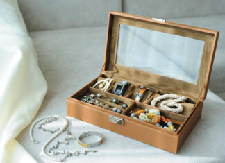 Leather Jewelry Box With Jewelry And Accessories Laid On A Couch