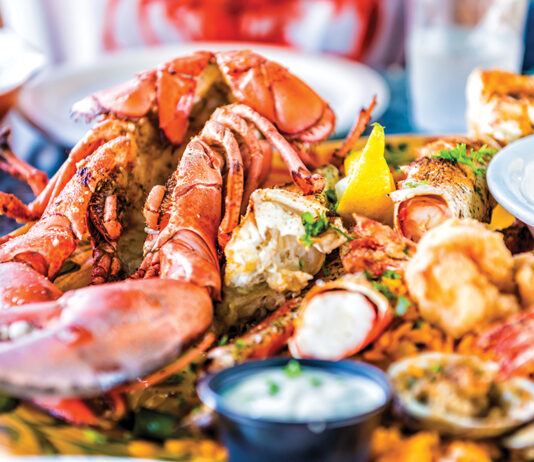 Macro Closeup Of Red Lobsters, Shrimp, Crab, Oyster And Seafood Platter On Plate In Restaurant With Tartar Sauce