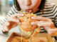Woman Eating A Hamburger In Modern Fastfood Cafe, Lunch Concept