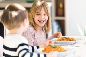 Smiling Children Having Fun While Eating Spaghetti With Tomato Sauce In The Kitchen At Home.