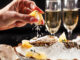 Prosecco Bar Concept. Open Oysters Lie On Crushed Ice With Lemon And Lime, Next To A Glass Of Champagne. Background Image. Copy Space.