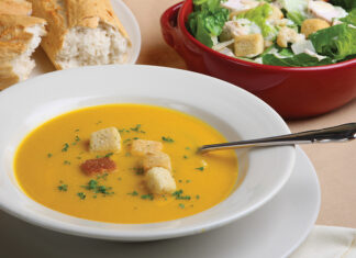Pumpkin Soup With Garnish, Bread And Salad In The Background